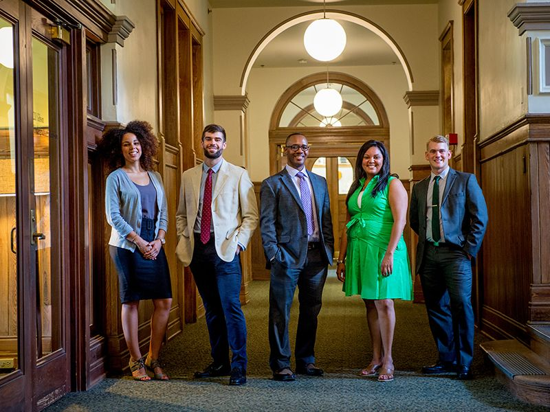 New admissions staff members pose in a hallway in Gibson Hall