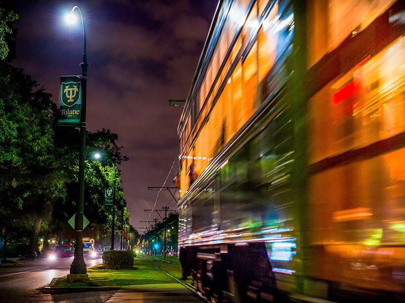 The streetcar passes by at night in front of Tulane.